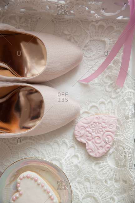 Light pink pumps and heart-shaped cookies on lace