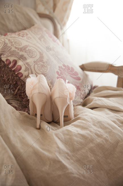 Light pink pumps on a chair with linen fabric