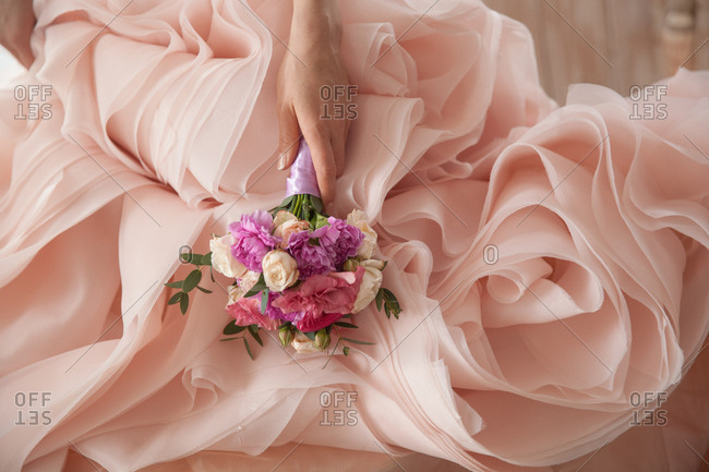 Woman in a light pink formal gown holding a bouquet of flowers