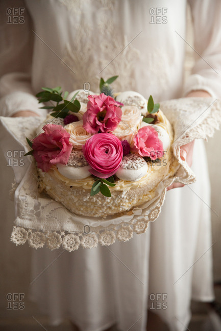 Woman in a white dress holding a cake decorated with flowers