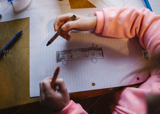 Little girl drawing on a piece of notebook paper with crayons