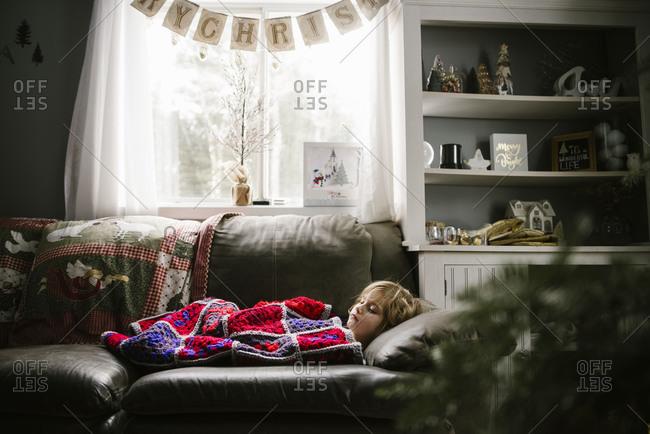 Girl lying under a crocheted blanket on a sofa