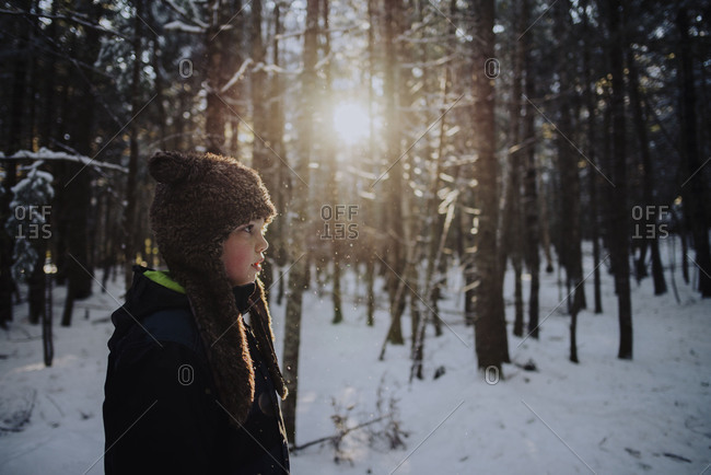 Boy in an earflap cap standing in a snowy forest
