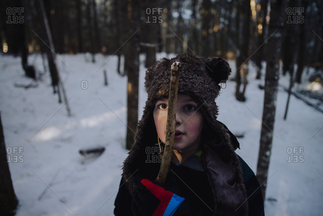 Boy standing in a snow-covered forest with a stick stuck to his face