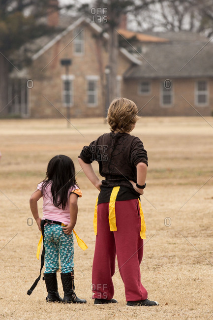 Two children standing in a field during a flag football game