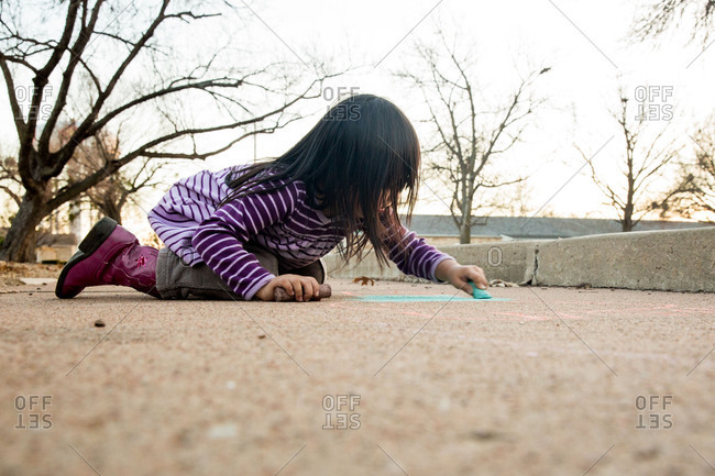 Little girl drawing on a sidewalk with chalk