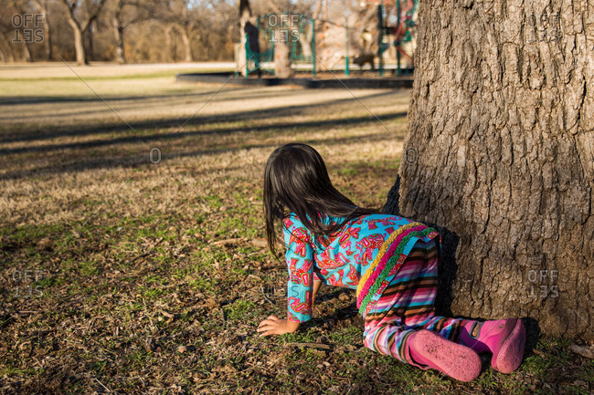 Little girl playing hide and seek behind a tree at a park