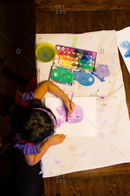 Little girl painting on a paper with watercolors