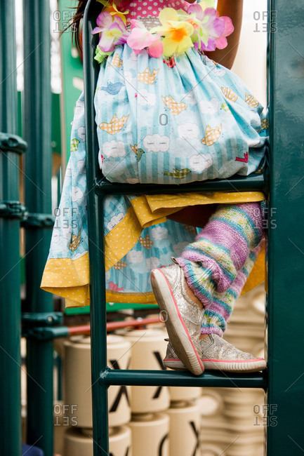 Little girl in colorful clothes sitting on a ladder at a playground