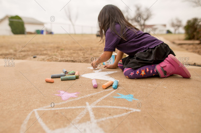 Little girl drawing artwork on a sidewalk with chalk