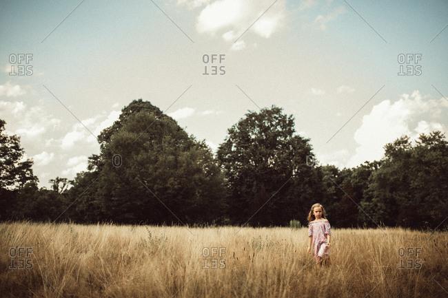 Girl walking alone in meadow