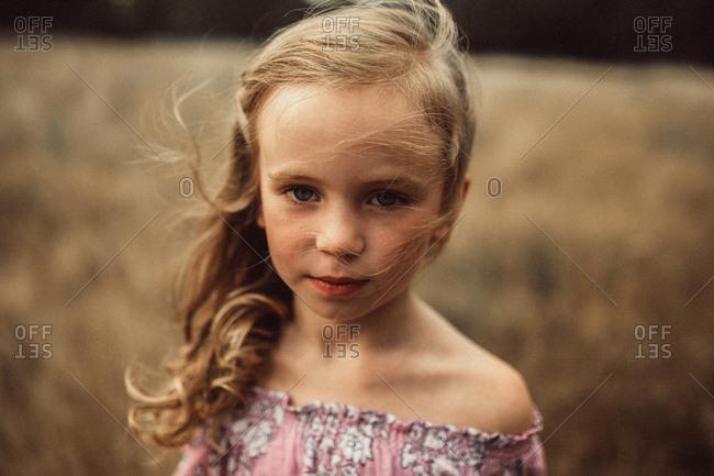 Portrait of girl in breeze in meadow