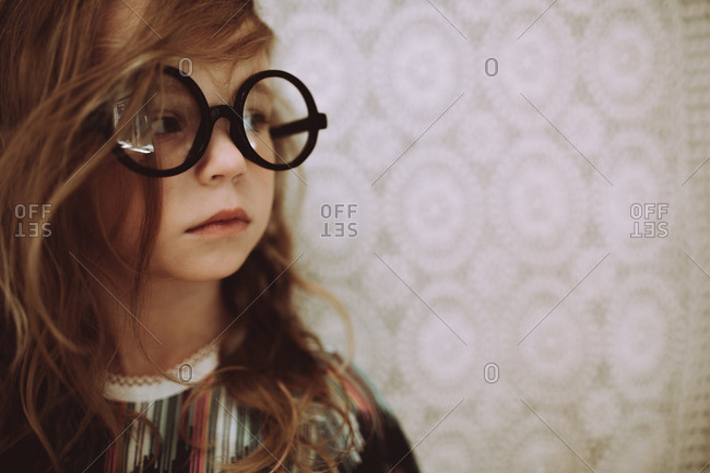 Girl in round glasses looking away