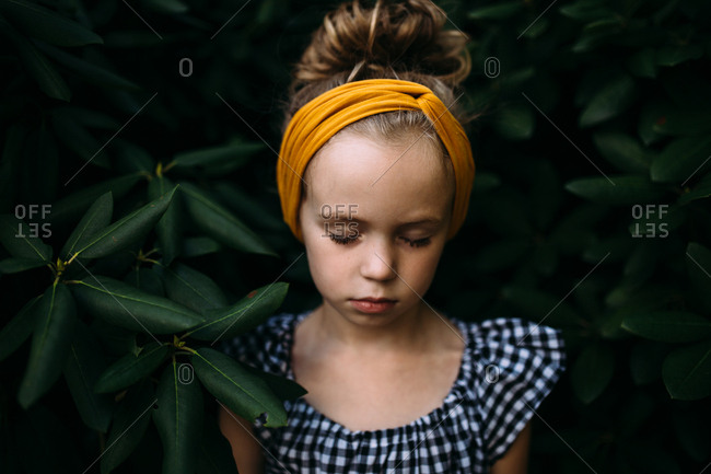 Girl with eyes closed by a bush