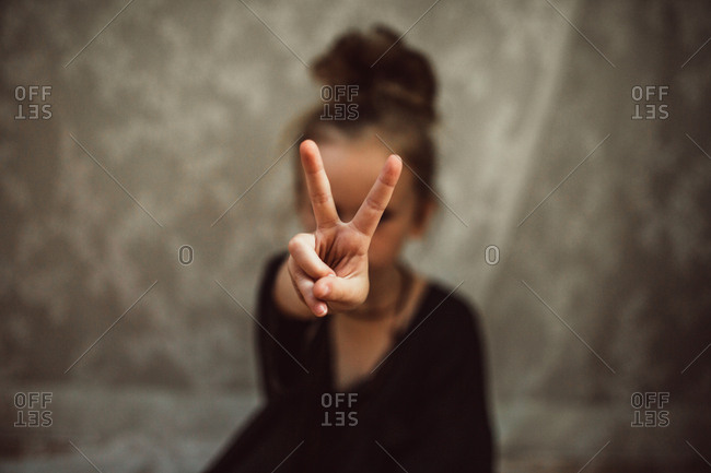 Girl making a peace sign with hand