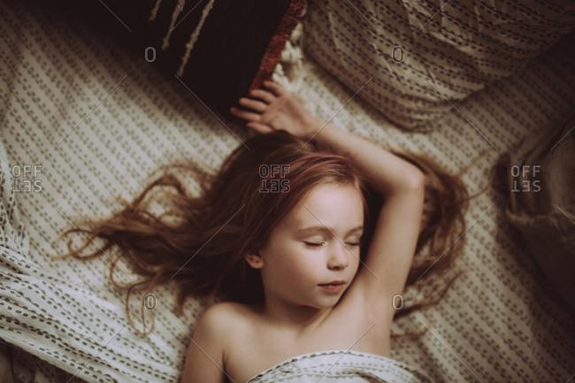 Girl sprawled asleep on her bed