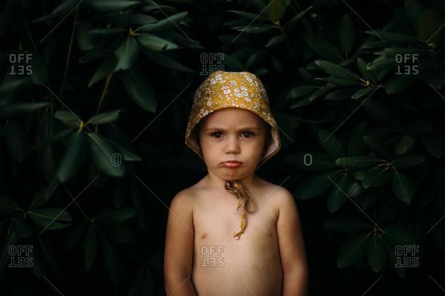 Girl by bush in a bonnet