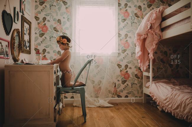 Girl sitting at desk in flowery bedroom