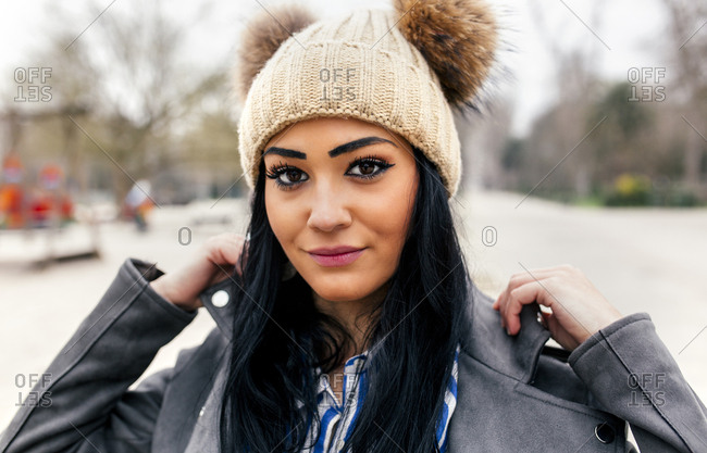 Young woman standing in a park wearing a toboggan with pompoms