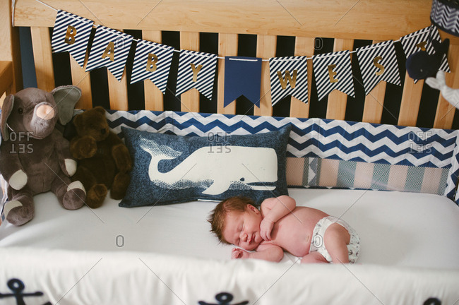 Baby boy sleeping in a nautical themed crib