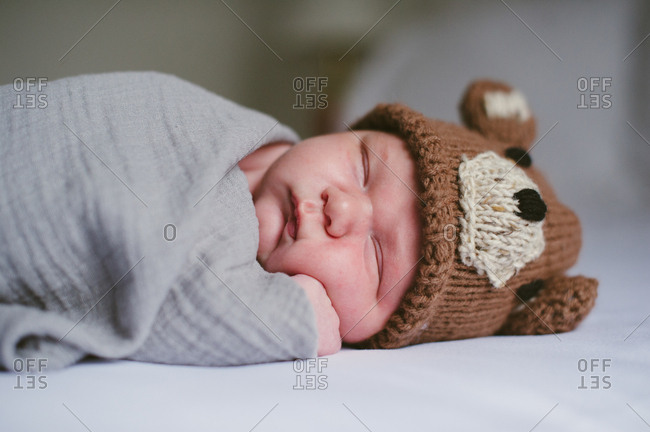 Newborn boy wrapped in a muslin blanket wearing a homemade knit hat