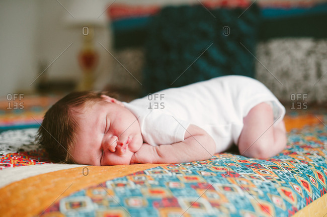 Baby boy sleeping on a colorful quilt on a bed