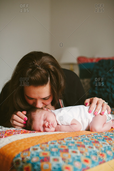 Mother kissing her sleeping infant son on a bed with a colorful quilt