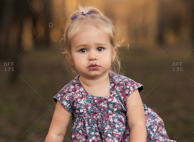 Portrait of little girl with blond hair and brown eyes seated outside in nature