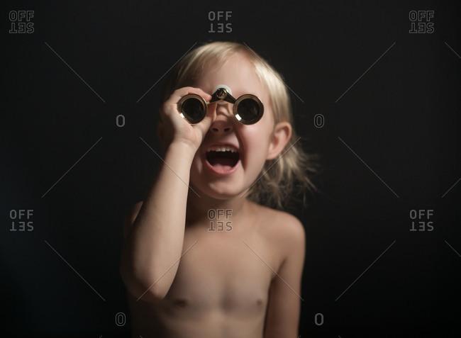 Portrait of laughing girl looking through binoculars