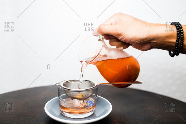 Straining tea into a cup