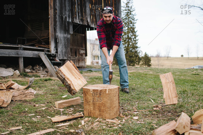 Man splitting firewood with an axe