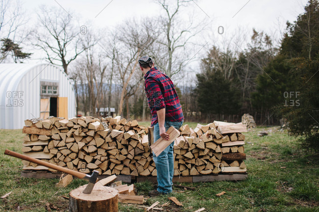 Man stacking firewood on a farm