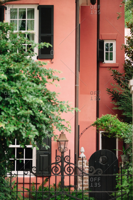 Wrought iron fence and windows on a pink home exterior