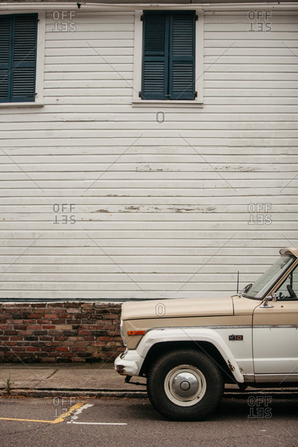 July 3, 2014: Retro automobile parked on a street beside a white historic building
