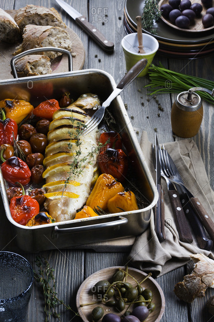 Fish with wedges of lemon and roasted vegetables in a roasting pan