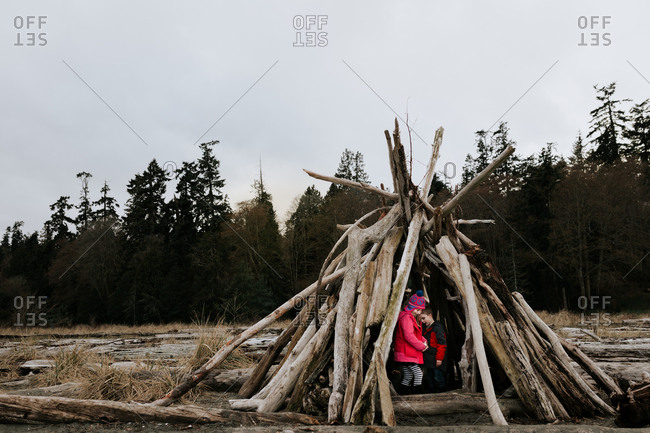 Two kids playing in a driftwood fort