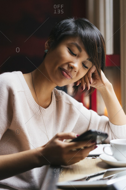 Young asian woman using her mobile phone from a coffee shop