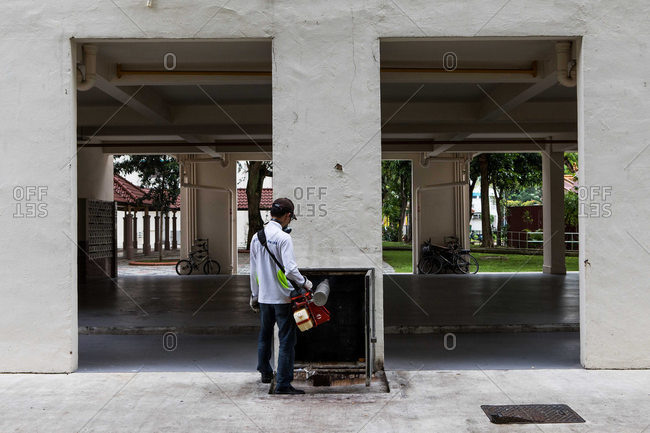 Singapore - October 24, 2016: Man fumigating apartment trash shoot