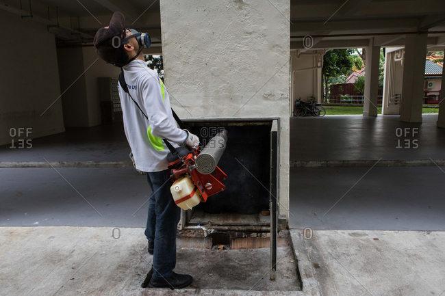 Singapore - October 24, 2016: Man fumigating housing complex trash shoot
