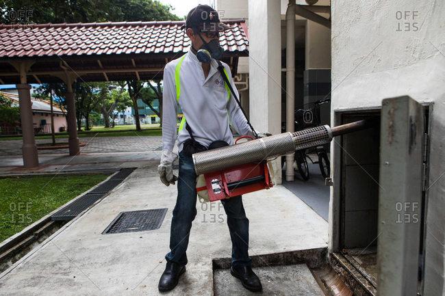 Singapore - October 24, 2016: Man fumigating an apartment trash shoot