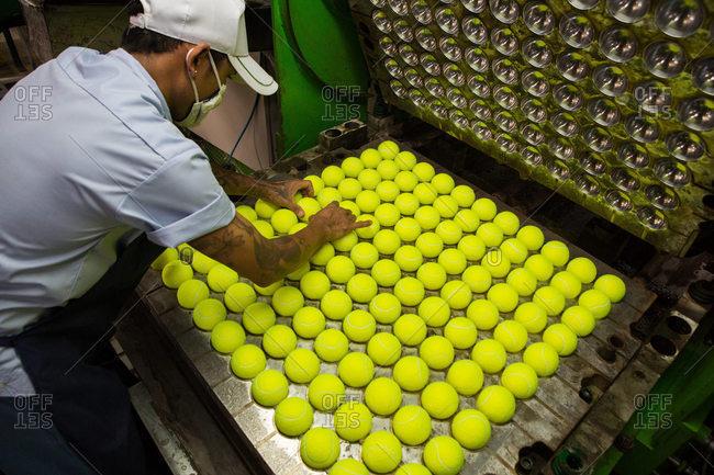 Nakhon Pathom, Thailand - August 18, 2016: Man putting tennis balls in hydraulic press