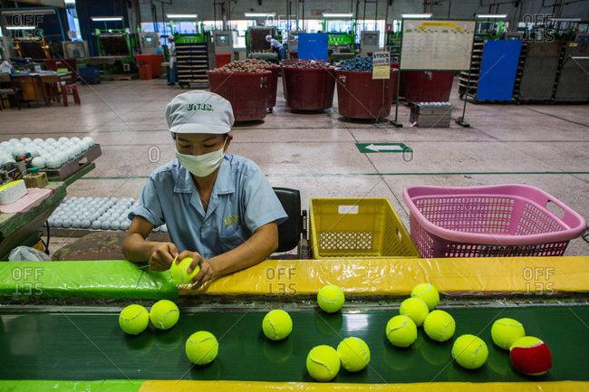 Nakhon Pathom, Thailand - August 18, 2016: Person checking tennis balls in factory