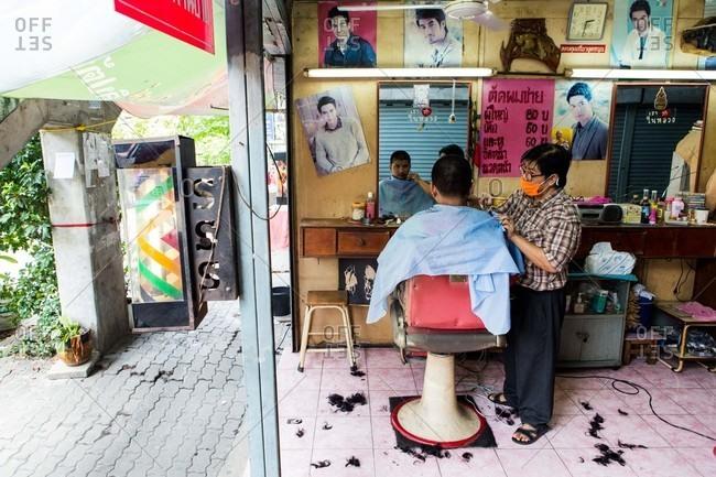 Bangkok, Thailand - July 24, 2016: Two men in barber shop
