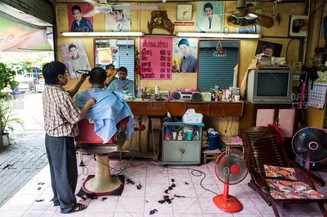 Bangkok, Thailand - July 24, 2016: Two men in a barber shop