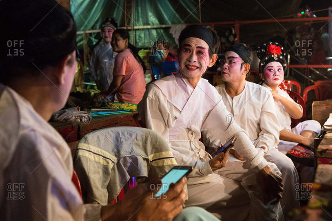 Nakhon Swan, Thailand - February 10, 2016: Theater performers with phones backstage