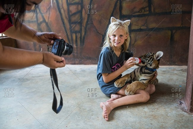 Kanchanaburi, Thailand - May 10, 2015: Girl feeding a baby tiger