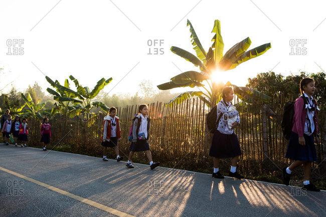 Thailand - January 26, 2015: Children walk to school in rural Thailand