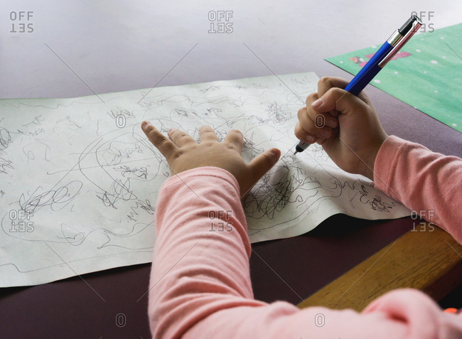 Young girl doodling on paper