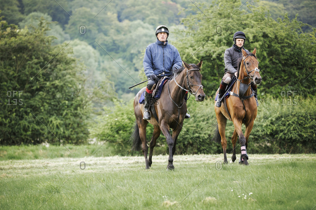 Two men on bay horses riding across a field side by side. Woodland.