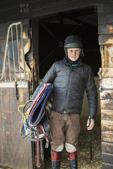 Man wearing a riding helmet and carrying  riding gear standing by a box stall.